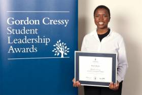 Dede Akolo smiles and holds a certificate next to a sign reading: Gordon Cressy Student Leadership Awards.