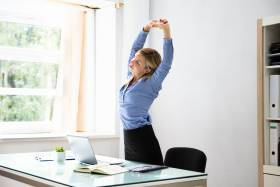 A woman stands beside a desk, stretching up with her arms above her head.