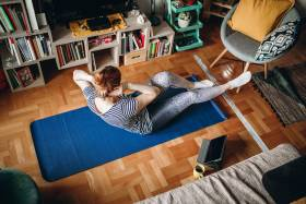A woman touches her elbow to her knee on a yoga mat on a living room floor.