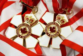 The Order of Canada medal is shaped like a six-petalled flower with a maple logo in the centre and a crown on the top petal.