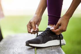 Close up on a person's hands tying a running shoe, on a bench outdoors.