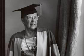In a historical photograph, Elsie McGill stands by a window, wearing her academic hat and robes.