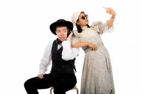 Man sitting on a stool, dressed an a pioneer shirt, vest and hat, listening to headphones.  A woman dressed in a pioneer dress and bonnet stands beside him, resting her elbow on his shoulder while she takes a selfie.