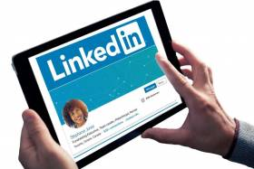 Tablet held to view LinkedIn profile webpage