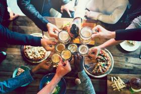 A group of friend cheersing glasses over a wood bar table full of snacks.