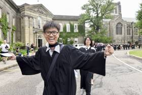 U of T grad in robes with arms outstretched in happiness, grinning at camera