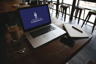 open laptop on a cafe table with the U of T logo on screen