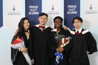 Group of new grad posing with their arms around each ohter's shoulders.