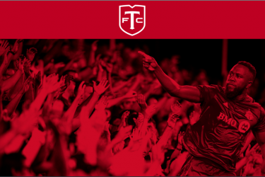 Red-tone image of TFC player pointing at the crowd.