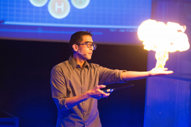 Man holding a fireball above his hand at a science demonstration