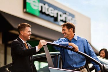 Man smiling as an Enterprise car rental employee shows him his rental car