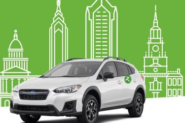 Zipcar against illustration of city skyline