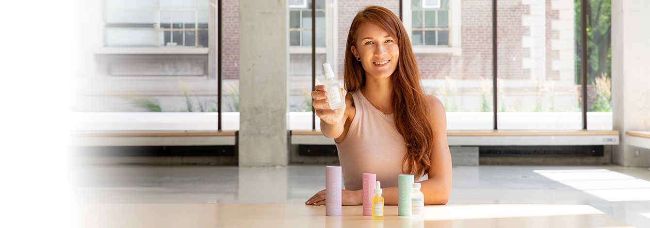 Laura Burget smiles and holds out a small bottle of cosmetics, sitting behind a desk with more products standing on it.