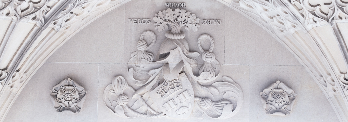 A close-up of the carved stone on the Soldiers' Tower memorial wall shows the U of T crest with tree, helmet, shield and knotted rope.